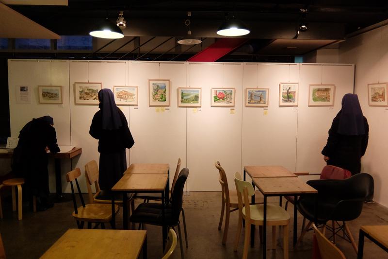 벽에 걸린 작품을 관람하는 관람객들의 모습