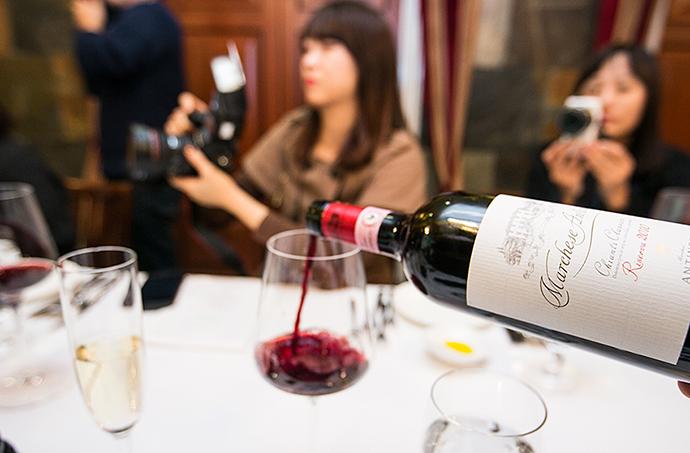 와인잔에 레드와인을 따르는 장면(측면)