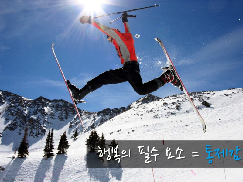 행복의 필수 요소 = 통제감. 스키장에서 점프를 하고 있는 스키어의 모습