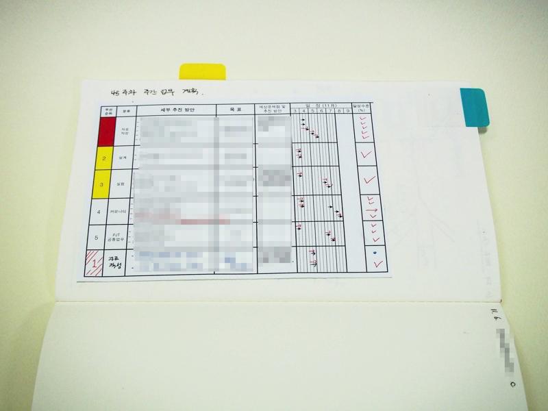 작성한 업무계획표를 노트에 붙여놓은 모습