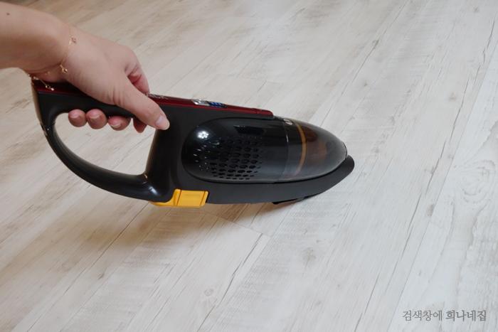작은 무선 청소기로 바닥을 청소하는 모습