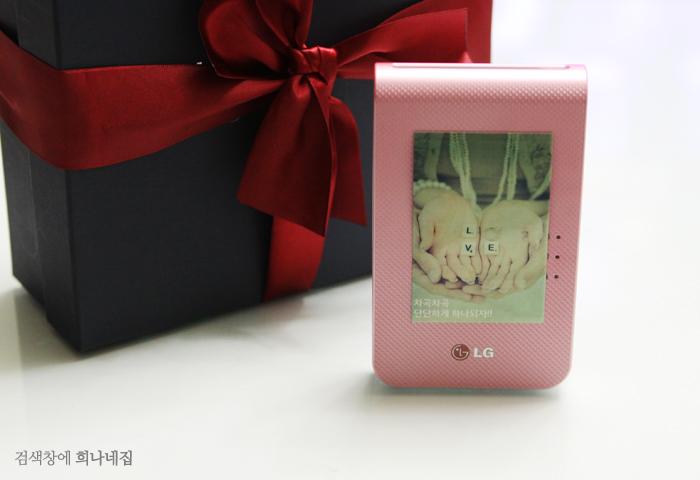 검은색 상자에 빨간 리본이 둘러져 있는 상자 앞으로 핑크색 포켓포토가 세워져 있다.