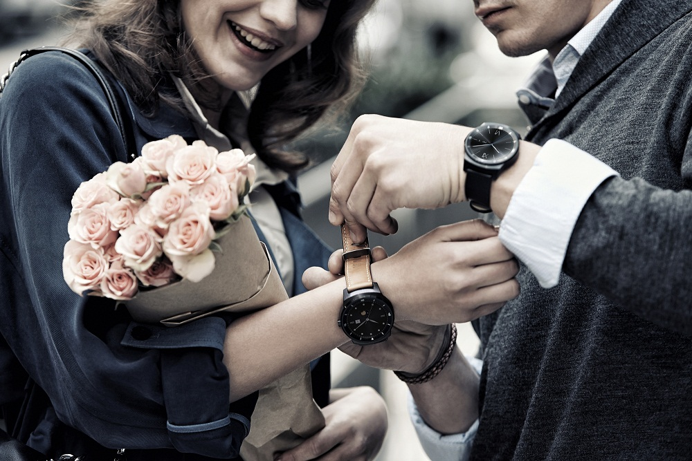 G워치 R을 착용하고 있는 한 남성이 꽃을 들고 있는 여성의 손목에 LG G워치R을 채워주고 있다.