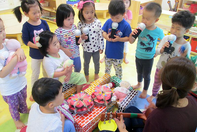어린이들이 선생님, 친구들과 어울려 함께 노래를 부르고 있다.