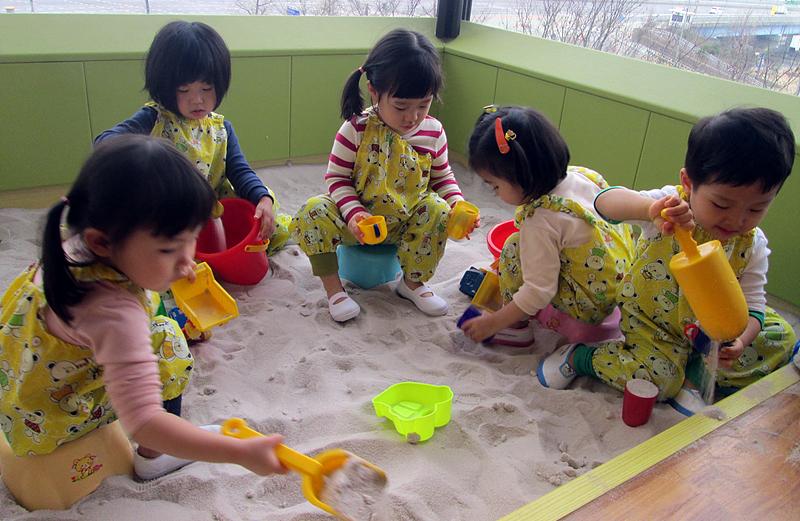 어린이집에서 모래놀이를 하며 놀고 있는 모습