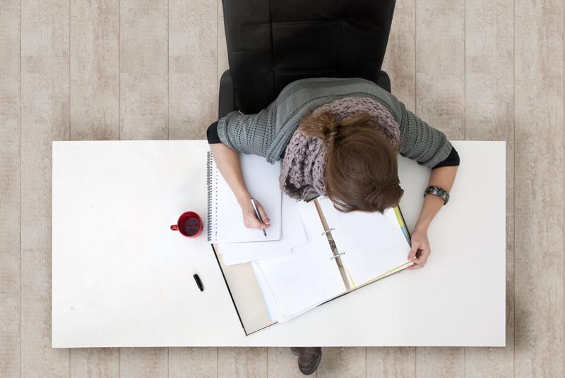 한 여성이 테이블에서 공부하고 있는 모습을 위에서 촬영한 사진.
