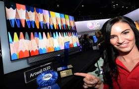 모델이 해외 각종 어워드를 수상한 LG 울트라올레드TV 앞에서 포즈를 취하고 있습니다.