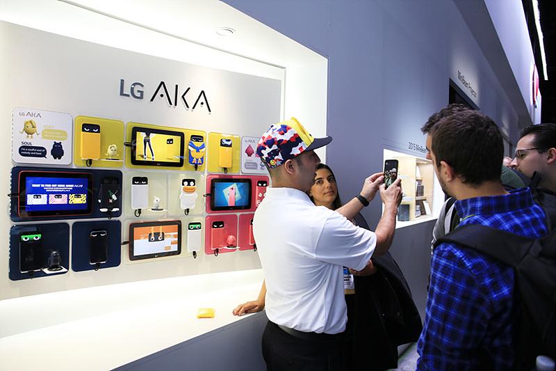 스냅백을 쓰고 LG AKA 스마트폰을 시연해 보고 있는 사람들