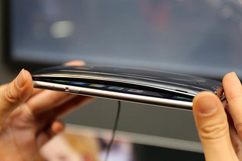 LG G플렉스2의 곡면 디자인을 강조하고 있는 이미지. 일반 스마트폰 위에 G 플렉스2를 겹쳐놓아 스마트폰 사이에 공간이 생긴 모습.