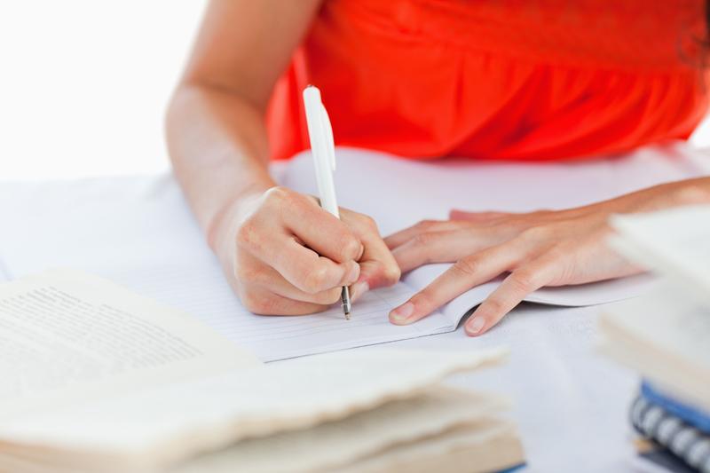 한 여성이 노트에 글을 쓰고 있다.