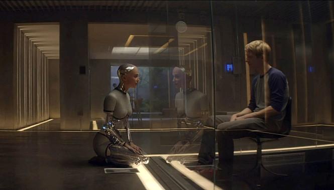 영화 '엑스 마키나' 의 한 장면, 주인공 로봇이 인간과 마주 앉아 있다.