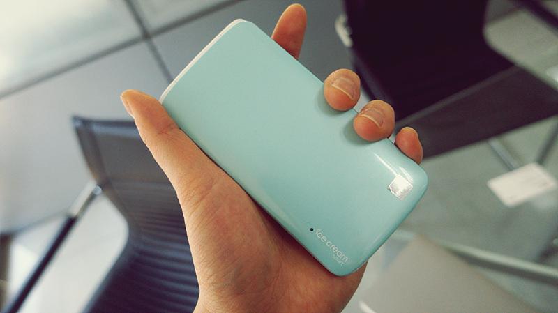 손으로 아이스크림 스마트 폴더 폰을 쥐고 있다. 휴대폰은 민트색이다.