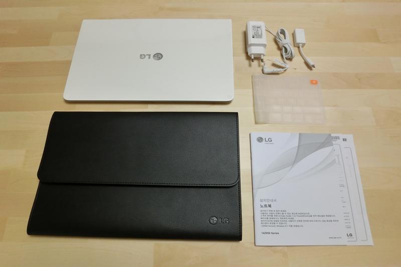 LG 그램14 노트북 구성품을 한 자리에 펼쳐놓았다. 노트북, 노트북 케이스, 충전 케이블, 사용설명서가 보인다.