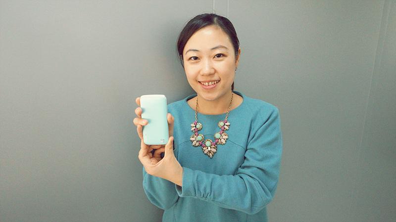 아이스크림 스마트 폴더폰의 기획에 참여한 LG전자 MC사업부 상품기획팀 이지영 과장이다. 민트색 휴대폰을 들고 청록색 옷을 입고 미소 짓고 있다.