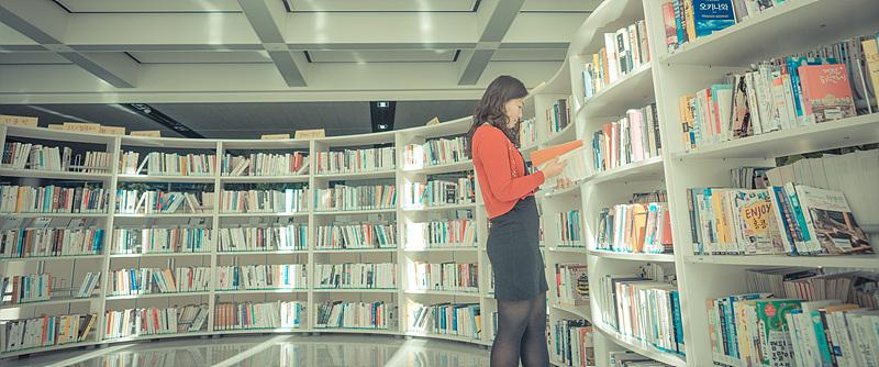 백경민 사원이 책장 앞에서 책을 보고 있다.