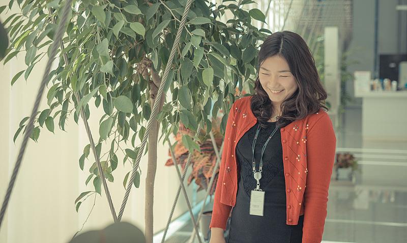 초록색 잎의 화분 옆에서 백경민 사원이 미소짓고 있다.