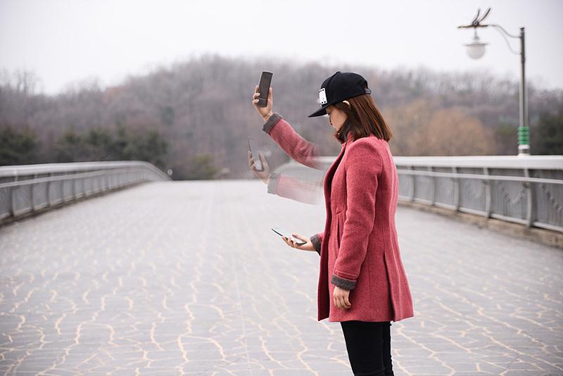 LG G 플렉스2의 '제스처 샷'을 시연하는모습. 팔을 아래로 내리면 촬영한 사진 확인이 가능하다.