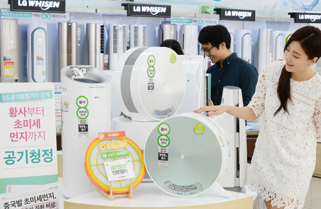 LG전자 모델이 매장에서  LG공기청정기를 소개하고 있습니다.