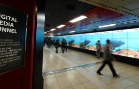 '디지털 미디어 터널'을 지나가는 시민들이 IPS디스플레이의 선명한 영상을 보고 있는 모습 입니다.