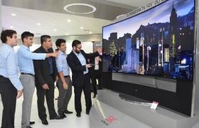 행사한 참가한 사람들이 LG전자 105형 울트라HD TV를 보고 있습니다.