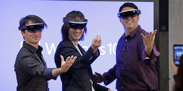 MS의 홀로렌즈 시연 장면. 성인 남성 3명이 홀로렌즈를 쓰고 손을 내밀고 있다.