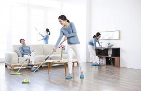 한 여성이 거실을 청소하고 있다.