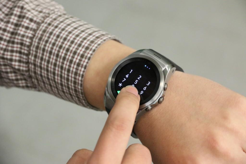 LG워치 어베인의 디스플레이에 보이는 다이얼을 손가락으로 누르고 있다.