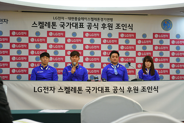 LG전자 스켈레톤 국가대표 공식 후원 조인식 현장. 네 명의 남녀 선수들이 파란색 단복을 입고 단상 테이블에 앉아있다.