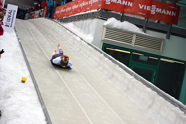 스켈레톤 대회에 참석한 한 선수가 엎드린 채 비탈진 경사면을 내려오고 있다.