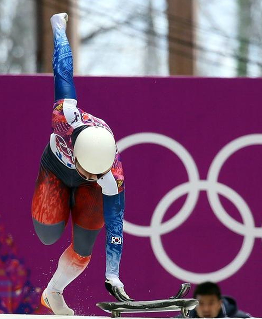 동계올림픽 스켈레톤 대회에서 한 남자 선수가 한 손을 들고 출발을 하고 있다.