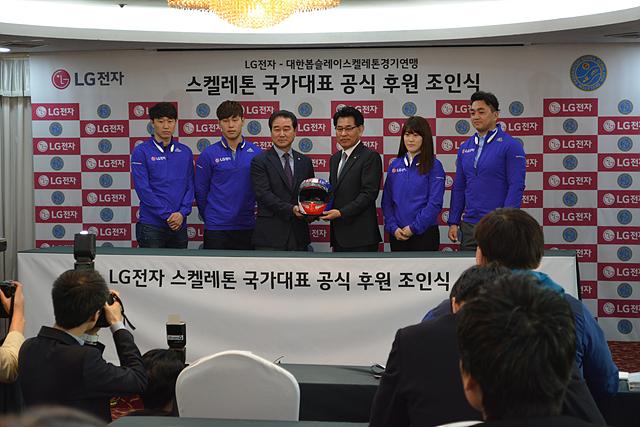 LG전자 스켈레톤 국가대표 공식 후원 조인식. 네 명의 남녀 선수 가운데 서 있는 두 명의 관계자가 헬멧을 마주 들고 포즈를 취하고 있다.