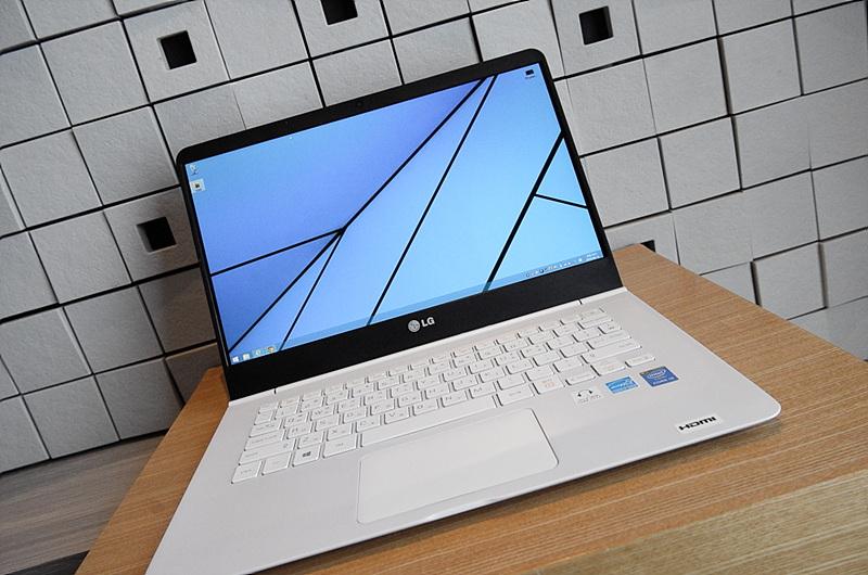 갈색 테이블에 놓인 LG 그램 14. 격자무늬 바탕화면이 보인다.