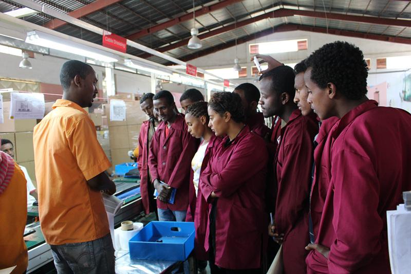 에티오피아 학생들이 직업훈련 학교에서 작업복을 입고 설명을 듣고 있다.