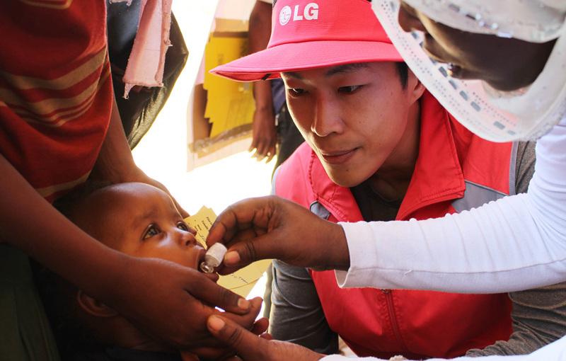 한 에티오피아 어린이에게 약을 먹이고 있는 모습과 그것을 지켜보는 LG전자 직원의 모습