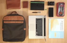 가방 속에 들어있는 물건을 하나씩 늘어놓아 정면에서 촬영한 모습. 가방, 파우치, 명함지갑, 노트북, 다이어리, 카메라, 스마트폰, 스케치북 등이 보인다.