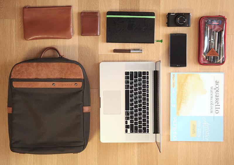 가방 속에 들어있는 물건을 하나씩 늘어놓아 위에서 촬영한 모습. 가방, 파우치, 명함지갑, 노트북, 다이어리, 카메라, 스마트폰, 스케치북 등이 보인다.