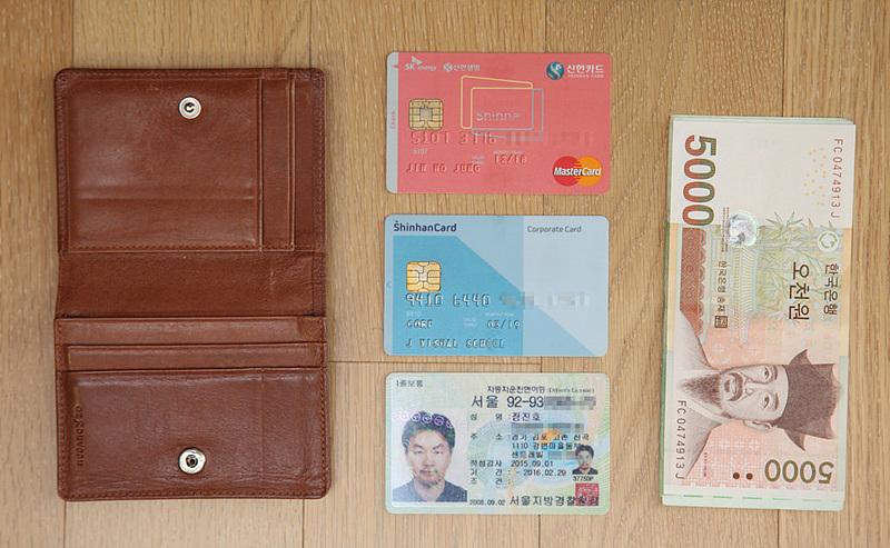 지갑 속에 들어있는 물건을 하나씩 꺼내놓은 모습. 카드, 면허증, 약간의 현금이 보인다.