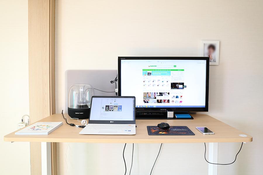 깔끔하게 정리된 테이블 위에 모니터, 노트북, 스마트폰이 놓여있다.