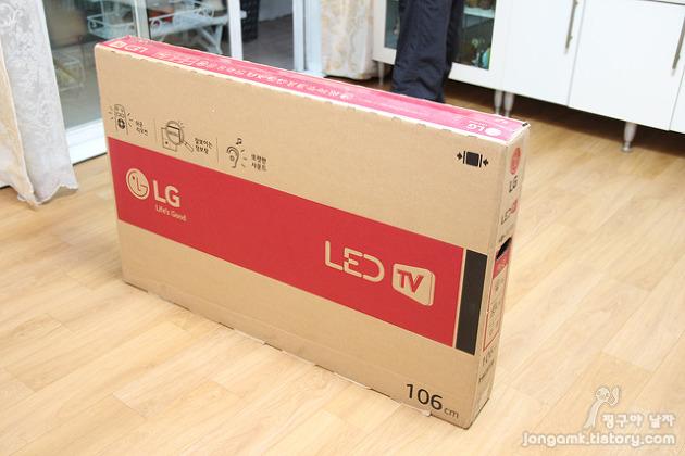 아직 박스 포장을 뜯지 않은 LG TV가 바닥에 놓여있다.