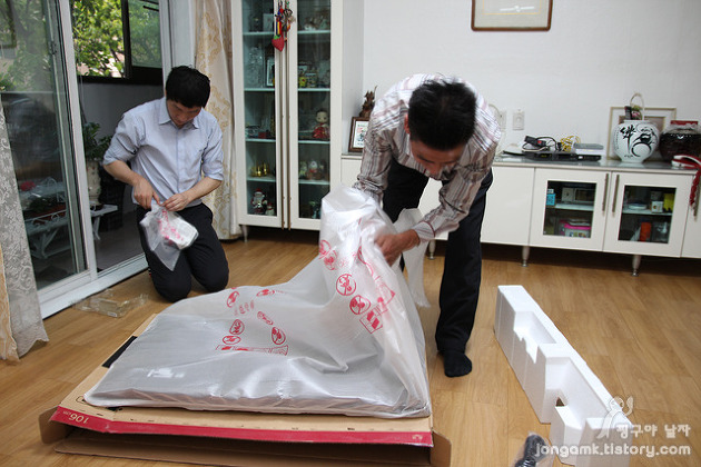 남자 설치기사 2명이 TV를 거실에 설치하고 있다.