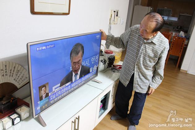 LG 이지 TV 벽걸이형. 장인어른이 설치된 TV를 만지고 있다.