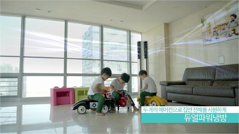 듀얼에어컨 CF 촬영 장면 중 하나. 거실에서 장난감 자동차를 타고 노는 삼둥이의 모습. 하단 우측 자막으로 두 개의 에어컨으로 집안 전체를 시원하게! 듀얼파워냉방 자막
