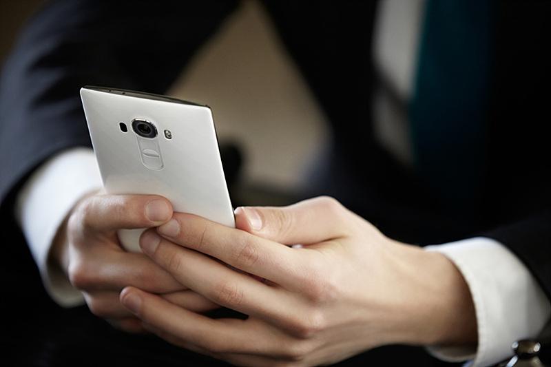 한 남성이 G4 화이트 세라믹 커버 스마트폰을 한 손에 들고있다.