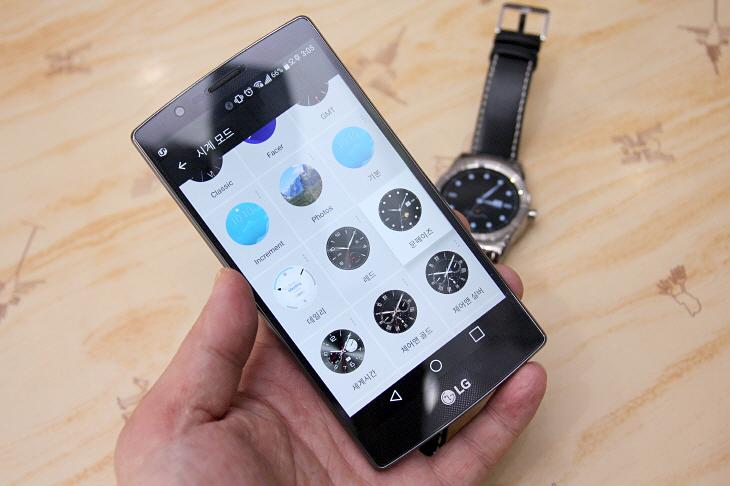스마트폰 화면으로 스마트워치의 시계 모드를 조정하고 있는 모습