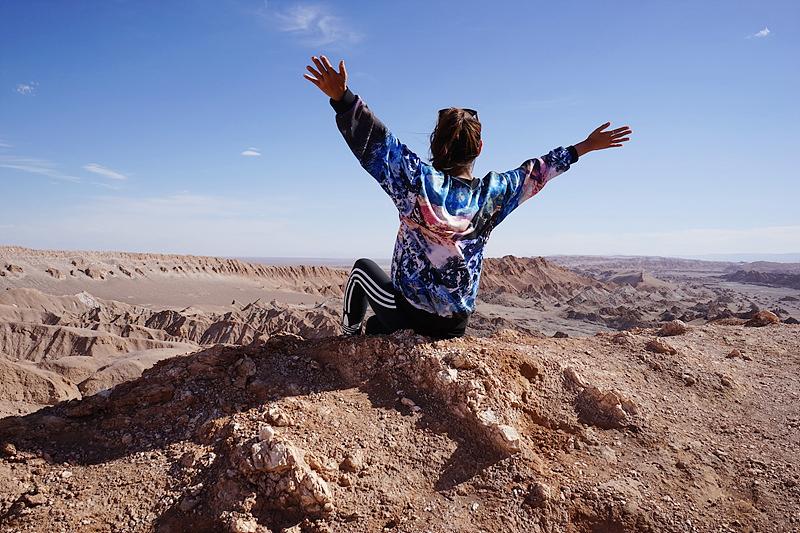 아타카마 사막에서 양 팔을 벌리고 앉아있는 최고야의 뒷모습