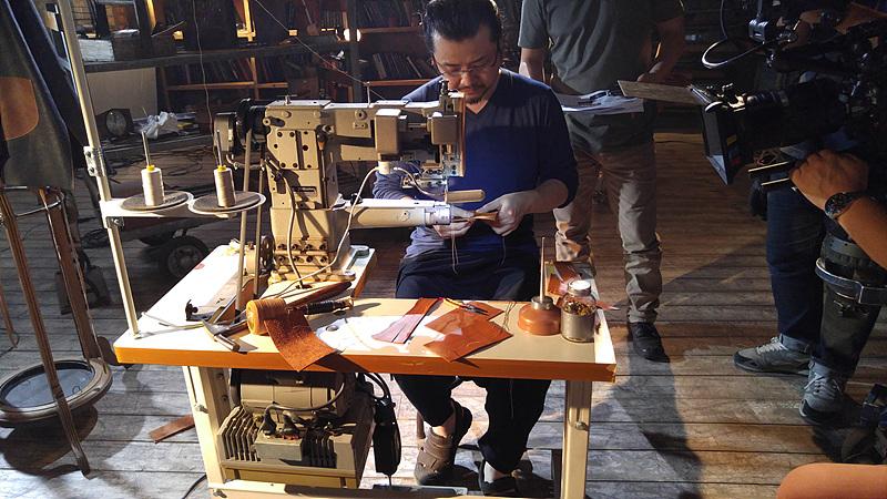 한 남성이 테이블 앞에 앉아 G4의 가죽 케이스에 스티치를 박고 있다.