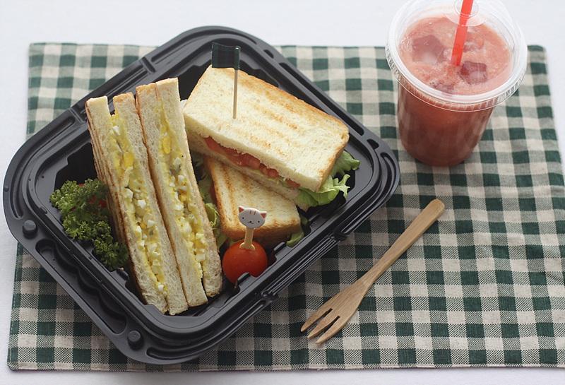 테이블보 위에 올려진 참치 샌드위치와 에그 샌드위치. 우측으로는 과일 주스가 놓여있다.