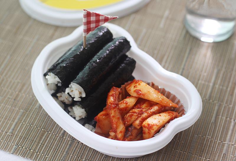 깃발 모양의 이쑤시개가 꽂혀있는 충무김밥. 매콤한 양념이 된 오징어가 함께 놓여있다.