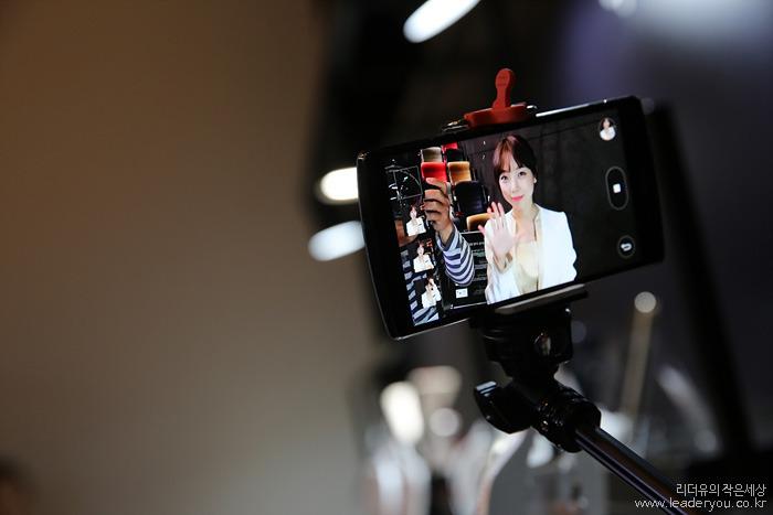 셀카봉을 이용해 전면 카메라로 제스쳐 샷을 촬영하고 있는 모습