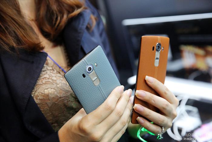 한 여성이 갈색 가죽 커버, 블루 가죽 커버의 G4를 양 손에 들고있다.